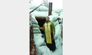 Військовий капелан о. Андрій Зелінський при вході в один із бліндажів на передовій.